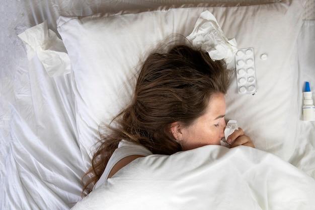 Una giovane donna malata a letto, sdraiata con la testa sotto la pila di fazzoletti di coperte accanto alla vista dall'alto.