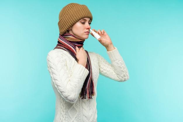 La giovane donna ammalata in sciarpa e cappello usa lo spray nasale isolato su priorità bassa blu - immagine