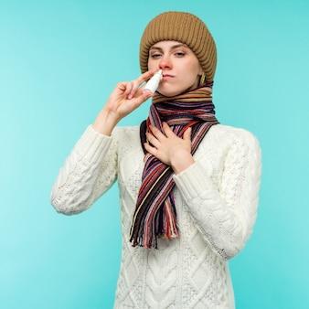 La giovane donna ammalata in sciarpa e cappello usa lo spray nasale isolato su priorità bassa blu