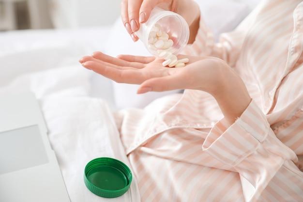 Giovane donna ammalata che prende le pillole a casa, primo piano