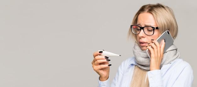 Giovane donna ammalata con gli occhiali ha preso freddo, guardando il termometro
