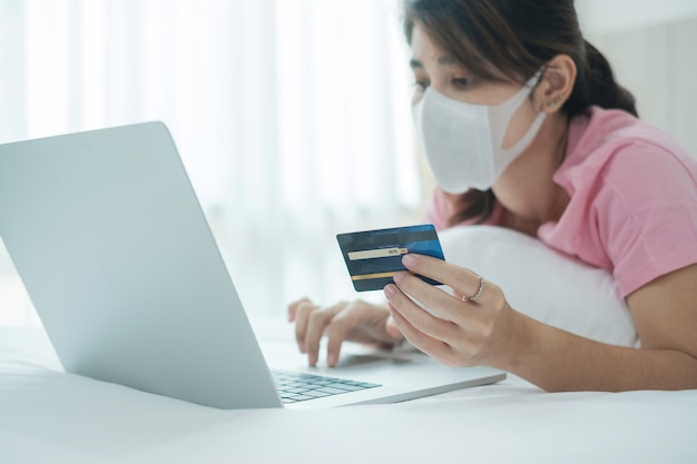 Donna di malattia con la carta di credito della tenuta della maschera di protezione e per mezzo del computer portatile del computer per acquisto online sul letto nella mattina a casa.