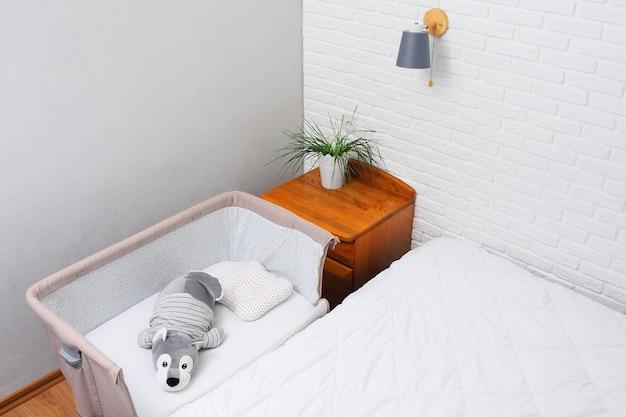 Letto laterale per un neonato sullo sfondo di un muro di mattoni bianchi