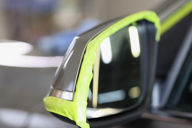 Lo specchietto laterale dell'auto ha un nastro protettivo verde per la lucidatura del servizio di lucidatura dell'auto di alta qualità quality