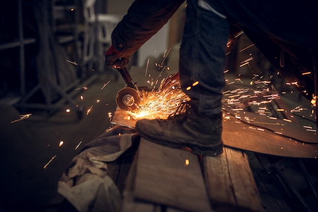 Vista alta vicina del lato del lavoratore del tessuto che lavora con lo strumento elettrico della smerigliatrice su una struttura d'acciaio nella fabbrica mentre volo delle scintille.