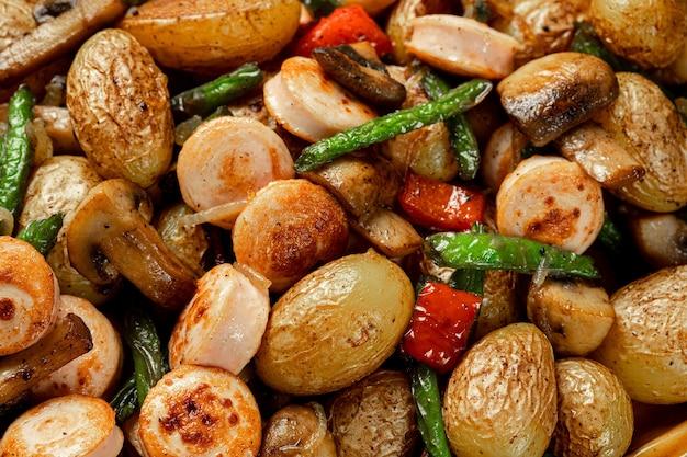 Contorno di verdure al forno asparagi fagioli, pepe, funghi e salsiccia, orientamento verticale. sfondo di pietra grigia. vista dall'alto