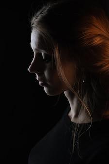 Side-face piuttosto giovane donna in posa isolato, ritratto su sfondo nero