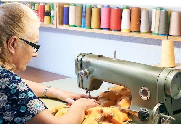 Immagine laterale di una donna anziana con gli occhiali che cuce un tessuto fantasia gialla con una macchina da cucire industriale illuminata dall'alto