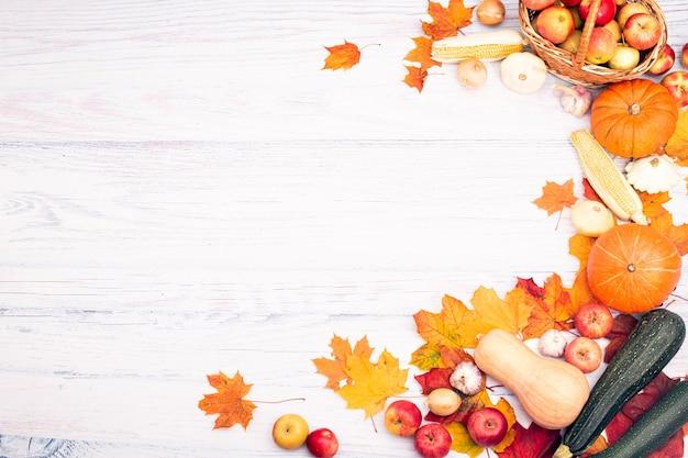 Layout laterale con zucca, mais, altre verdure e foglie d'autunno. vista dall'alto su uno sfondo di legno chiaro. autunno laici piatta.