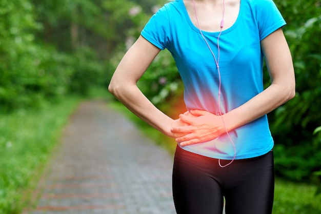 Dolore laterale - crampi laterali del corridore della donna dopo la corsa. fare jogging donna con dolore al lato dello stomaco dopo il jogging si allena. atleta femminile. Foto Premium