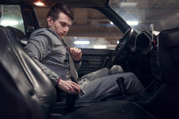 Foto laterale del conducente maschio che allaccia la cintura di sicurezza mentre è seduto in macchina