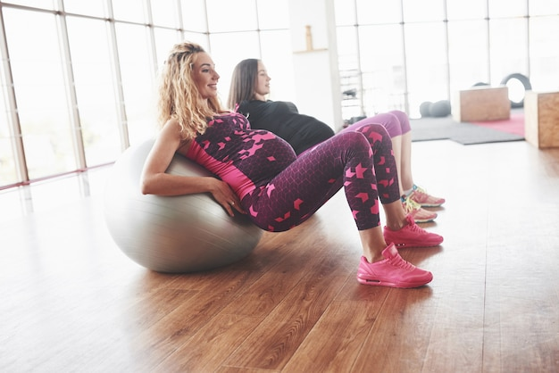 Foto laterale di due donne incinte che fanno esercizi di fitness usando palle di stabilità.