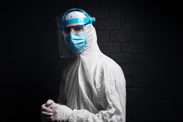 Ritratto laterale del medico che indossa la tuta dpi contro il coronavirus e il covid-19.