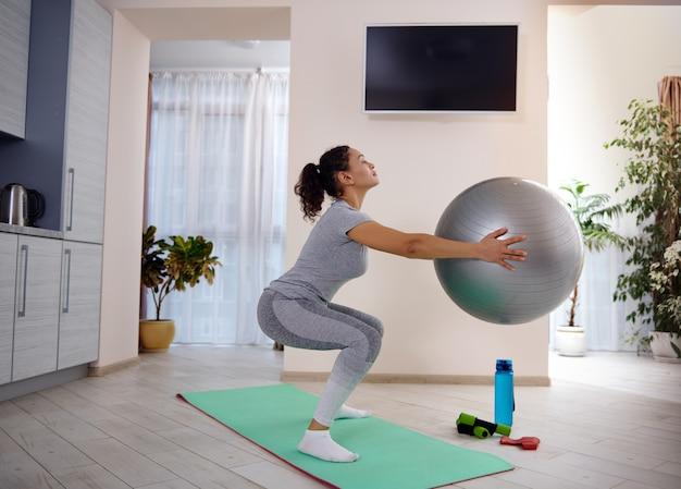 Ritratto laterale di una donna sportiva che tiene una palla fitness e accovacciata su una stuoia di yoga. allenarsi a casa