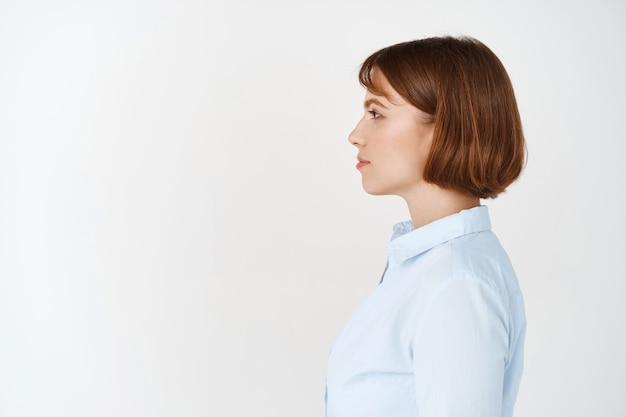 Ritratto laterale di giovane imprenditrice con i capelli corti, con indosso una camicetta da ufficio, guardando a sinistra lo spazio della copia con una faccia seria, in piedi sul muro bianco