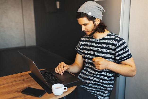 Ritratto laterale di giovane uomo bello che lavora a casa sul computer portatile; tazza di caffè e smartphone sul tavolo di legno.