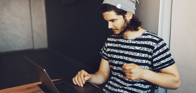 Ritratto laterale di giovane uomo bello che lavora a casa sul computer portatile. vista panoramica del banner.