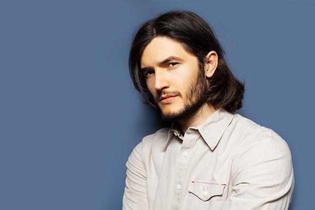 Ritratto laterale di giovane uomo serio con capelli lunghi che distoglie lo sguardo. sfondo di colore blu con copia spazio.