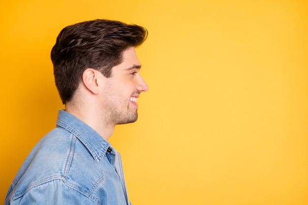 Profilo laterale vicino foto di allegro uomo positivo trentadue denti sognando comtemplando lo spazio vuoto di fronte a lui isolato muro di colori vivaci