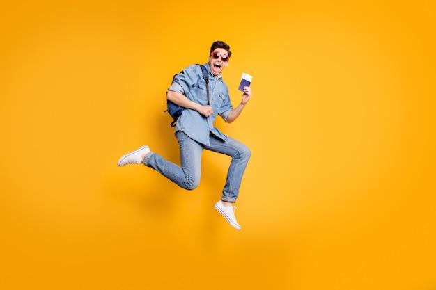 Foto di dimensioni del corpo a figura intera di profilo laterale di uomo pazzo urlante che tiene il biglietto del passaporto con le mani in calzature bianche vicino alla parete di colore giallo vivido isolato spazio vuoto