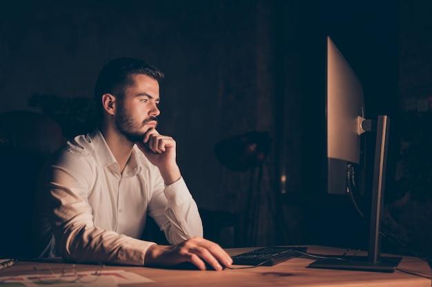 Il profilo laterale del programmatore pensieroso che lavora fuori orario pensa al mento del dito