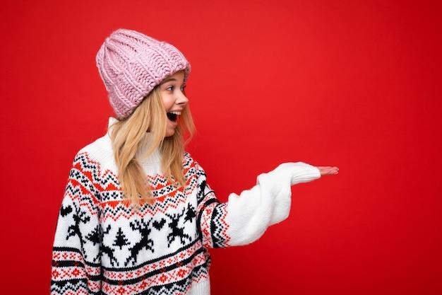 Foto del profilo laterale di una giovane donna bionda felice sorpresa piuttosto sorpresa in piedi isolata su una parete di sfondo colorata che indossa abiti alla moda di tutti i giorni che guardano di lato. copia spazio