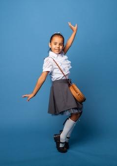 Foto del profilo laterale di una studentessa, felice sorriso positivo, salta, cammina, isolata su sfondo blu
