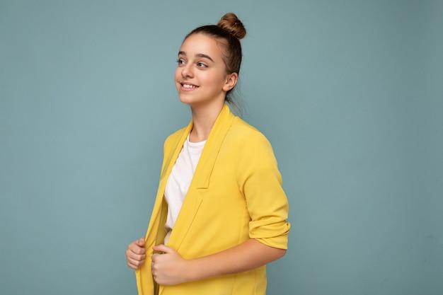 Colpo di profilo laterale della bambina castana sorridente felice positiva attraente che porta giacca gialla casuale e maglietta bianca