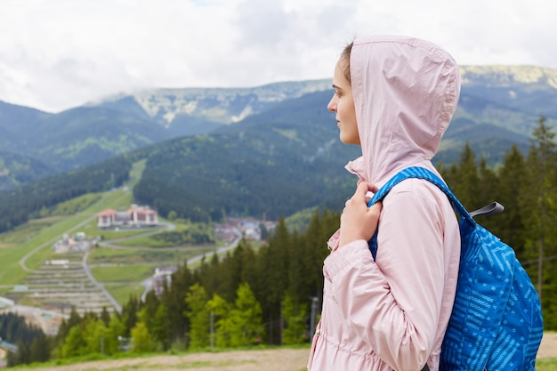Vista laterale di profilo di bella ragazza attraente, con giacca casual rosa e zaino blu, zaino in spalla femminile e vagabondaggio