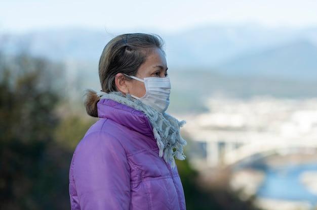 Vista del profilo laterale di una donna di mezza età che indossa una maschera bianca per la protezione contro covid19