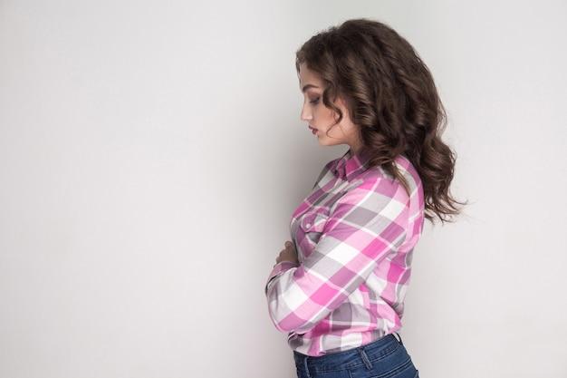 Vista di profilo laterale di una ragazza triste e infelice con camicia a scacchi rosa, acconciatura riccia in piedi, mani incrociate, tenendo la testa bassa e sentendosi di cattivo umore. girato in studio al coperto, isolato su sfondo grigio.