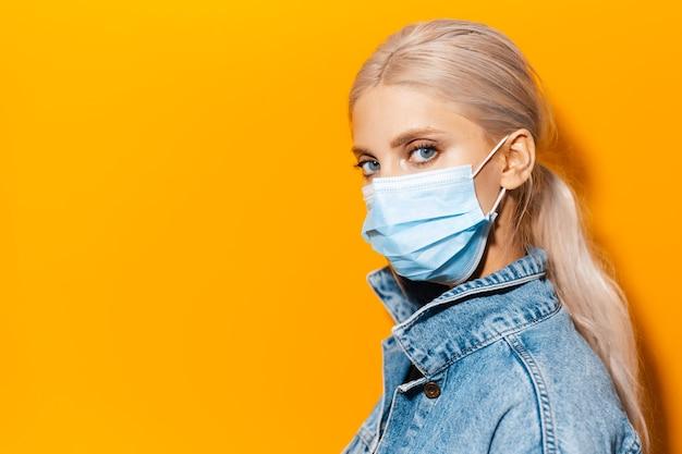 Ritratto in studio laterale di una giovane ragazza bionda che indossa una maschera medica contro il coronavirus su sfondo di colore arancione.