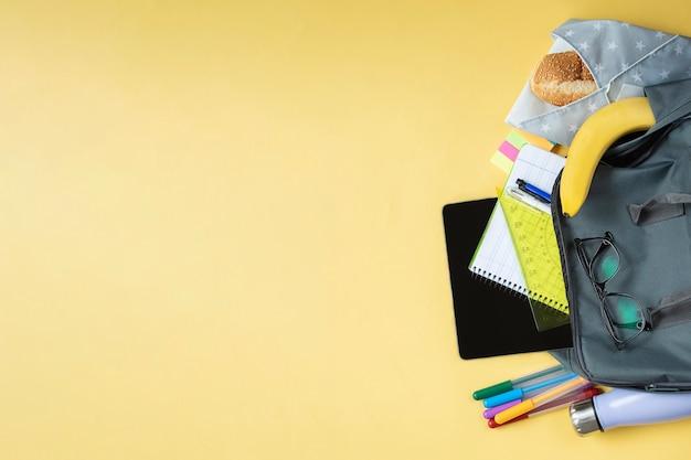 Vista dall'alto laterale dello zaino degli studenti con sandwich di materiale scolastico in un involucro riutilizzabile e bottiglia d'acqua metallica su superficie gialla yellow