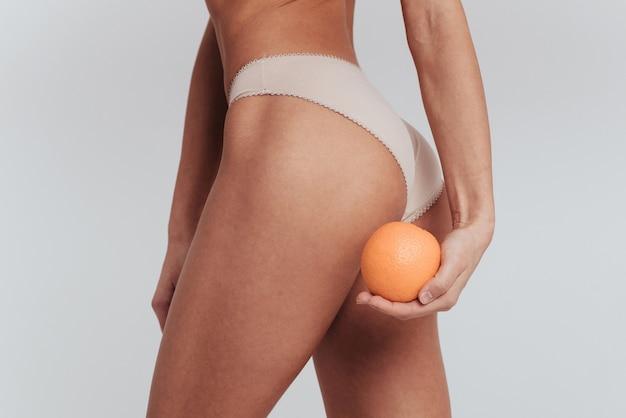 Giro laterale. foto di particelle di ragazza in biancheria intima bianca in piedi al muro bianco e tenendo l'arancia.