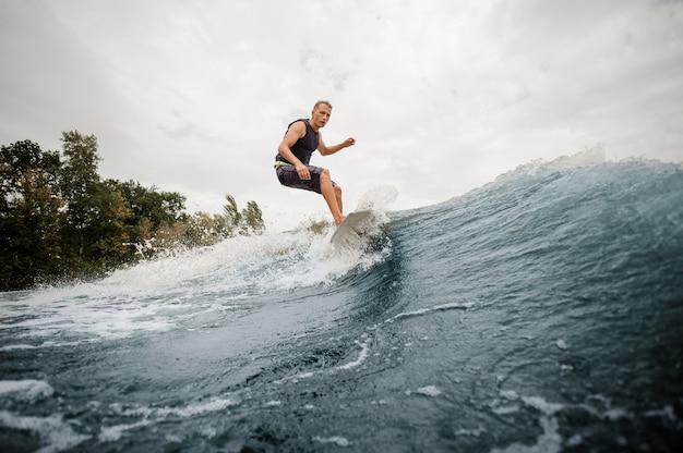 Ragazzo attivo di vista laterale che guida sul wakeboard bianco