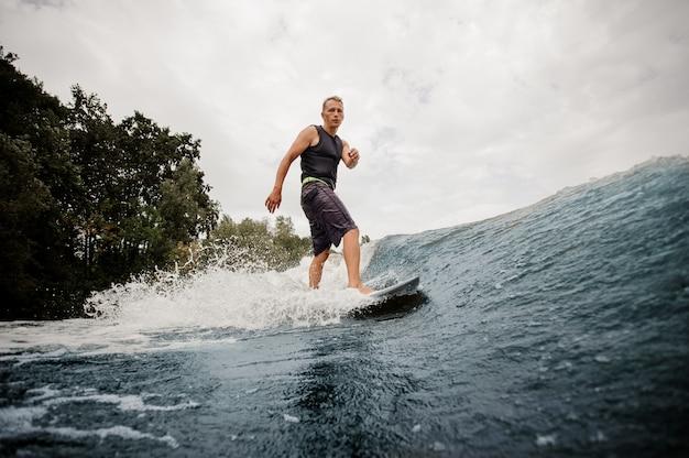 Ragazzo attivo di vista laterale che sta sul wakeboard bianco