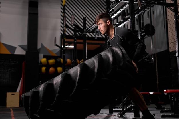 Vista laterale sull'uomo attivo lavora sodo - ribaltamento pneumatico in allenamento crossfit, uomo che utilizza attrezzature sportive. cross fit e allenamento. atleta forte e bello.
