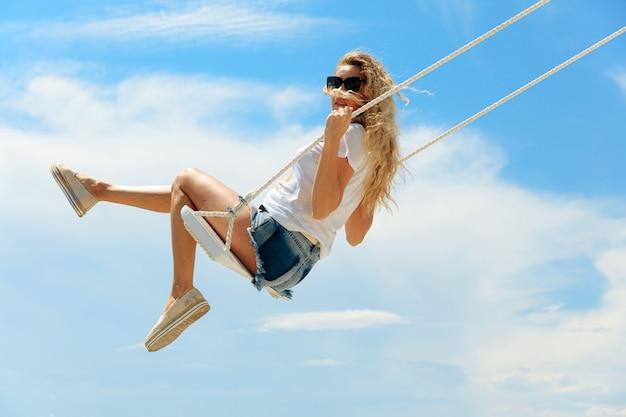 Vista laterale della giovane donna adorabile in abito estivo che oscilla in alto sopra il cielo blu. affascinante signora che si rilassa all'aperto durante il tempo libero estivo.