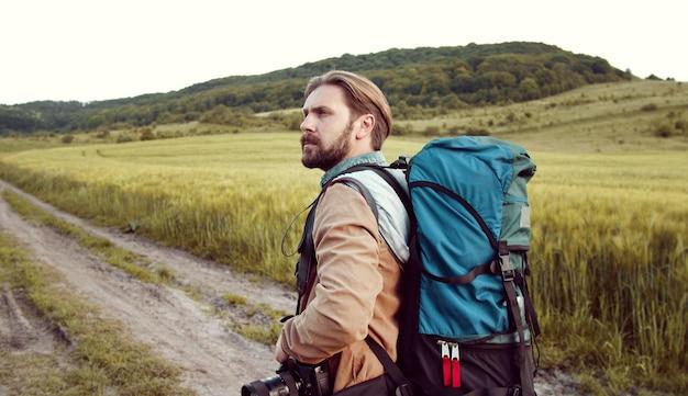 Vista laterale dell'escursionista setolato adulto che cammina nella natura verde sulla strada di campagna guardandosi intorno, mezza lunghezza