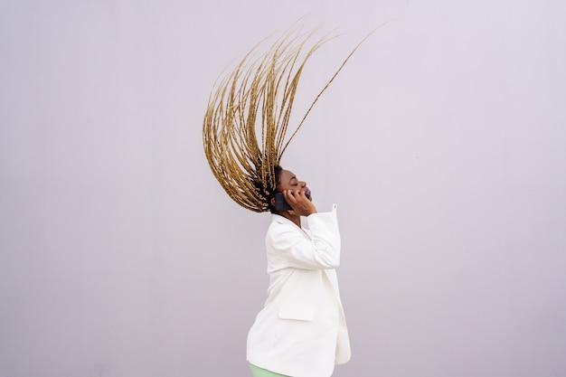 Vista laterale di una donna afroamericana che usa un telefono cellulare con gli occhi chiusi e le trecce gialle in aria. donna vestita con una giacca bianca e parlando al cellulare.