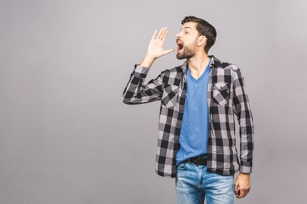Vista laterale di un gridare arrabbiato dell'uomo isolato sulla parete grigia