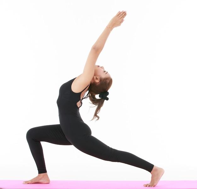 Vista laterale di una donna asiatica che fa una posa di affondo a mezzaluna con le braccia alzate mentre pratica yoga su sfondo bianco