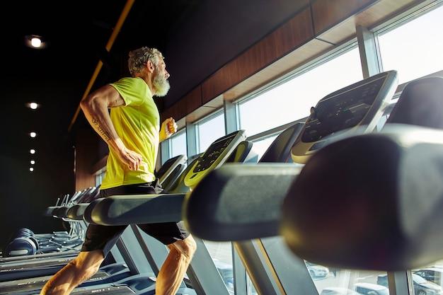 Vista laterale di un uomo atletico di mezza età in abbigliamento sportivo che corre su un tapis roulant in una palestra che fa cardio