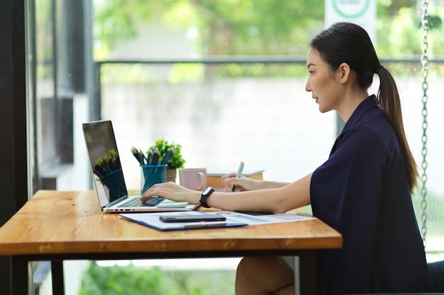 Vista laterale di una donna d'affari asiatica attraente che lavora al computer portatile nell'area di lavoro in ufficio con vista esterna sfocata sullo sfondo