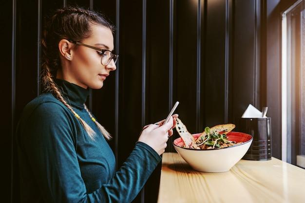 Vista laterale della ragazza attraente con le trecce seduto nel ristorante accanto alla finestra e scattare foto del suo pranzo sano.