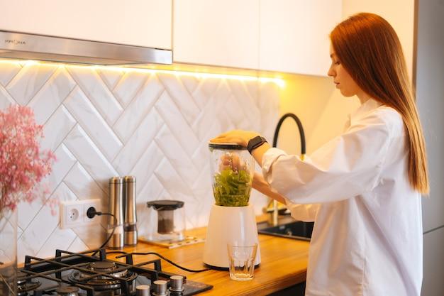 Vista laterale di una giovane donna rossa attraente che produce un succo di frullato di disintossicazione vegetale sano nel frullatore