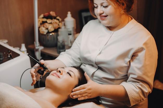 Vista laterale di una donna attraente che fa ossigenoterapia in un centro termale e benessere da un cosmetologo femminile.