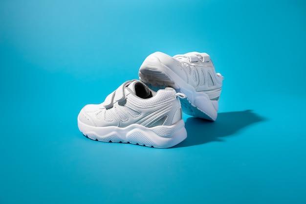 Vista laterale di una composizione equilibrata di due sneakers bianche in kid con velcro su sfondo di carta blu...