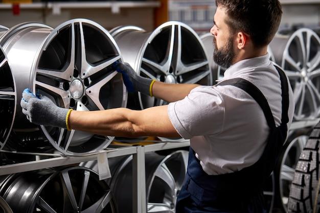 Vista laterale sul maschio barbuto meccanico auto riparatore esaminando cerchioni di auto, controllando l'assortimento nel suo negozio, al posto di lavoro, indossando l'uniforme
