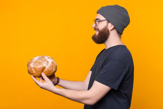 Vista laterale dell'uomo barbuto che dà a qualcuno un pane appena sfornato